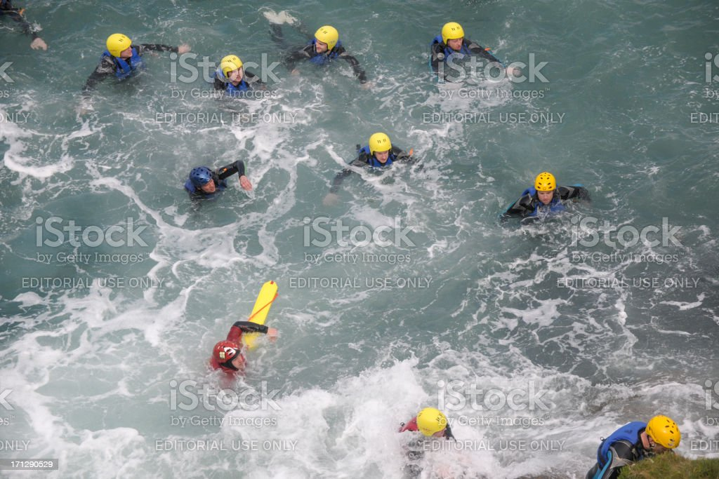 Coasteering, swimmers aproaching the rocks at Newquay Cornwall stock photo