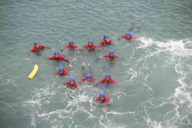 coasteering, swimmers aproaching the rocks at newquay cornwall - cornwall stock photos and pictures