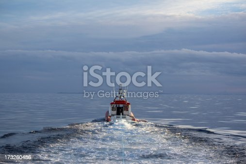 New Zealand Coastguard jet powered inflatable towing a broken down boat in the Hauraki Gulf of New Zealand. Unruly weather is seen in the distance.
