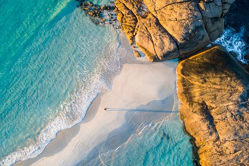 Coastline aerial photograph of aquamarine ocean and man walking along white sandbar beach in Australia
