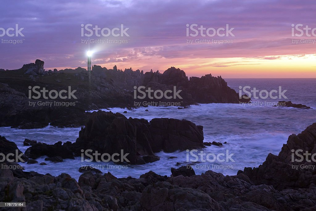 coastline and lighthouse at dusk stock photo