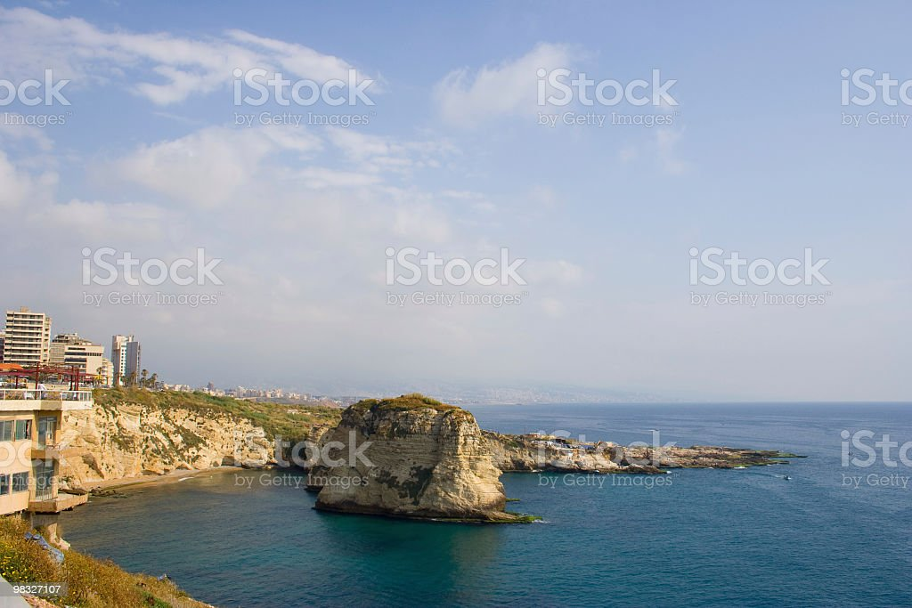 Coastline with rock feature and high rise buildings royalty-free stock photo