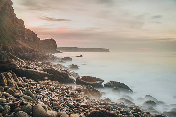 Coastside at sunset Some rocks emerging from the sea. Long exposure effect to give softness to the water rocky coastline stock pictures, royalty-free photos & images