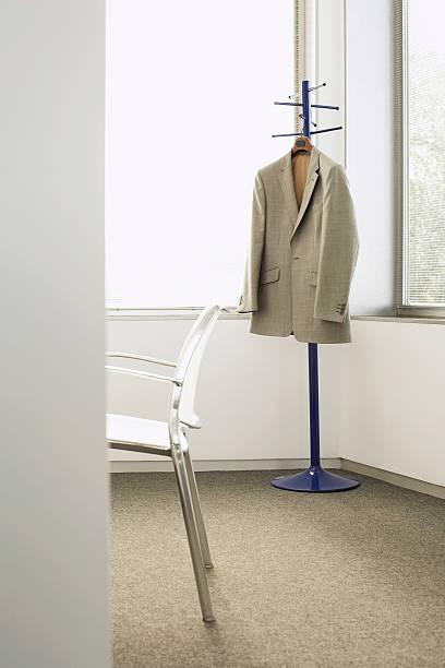 mantel und stuhl im büro - garderobenhaken stock-fotos und bilder