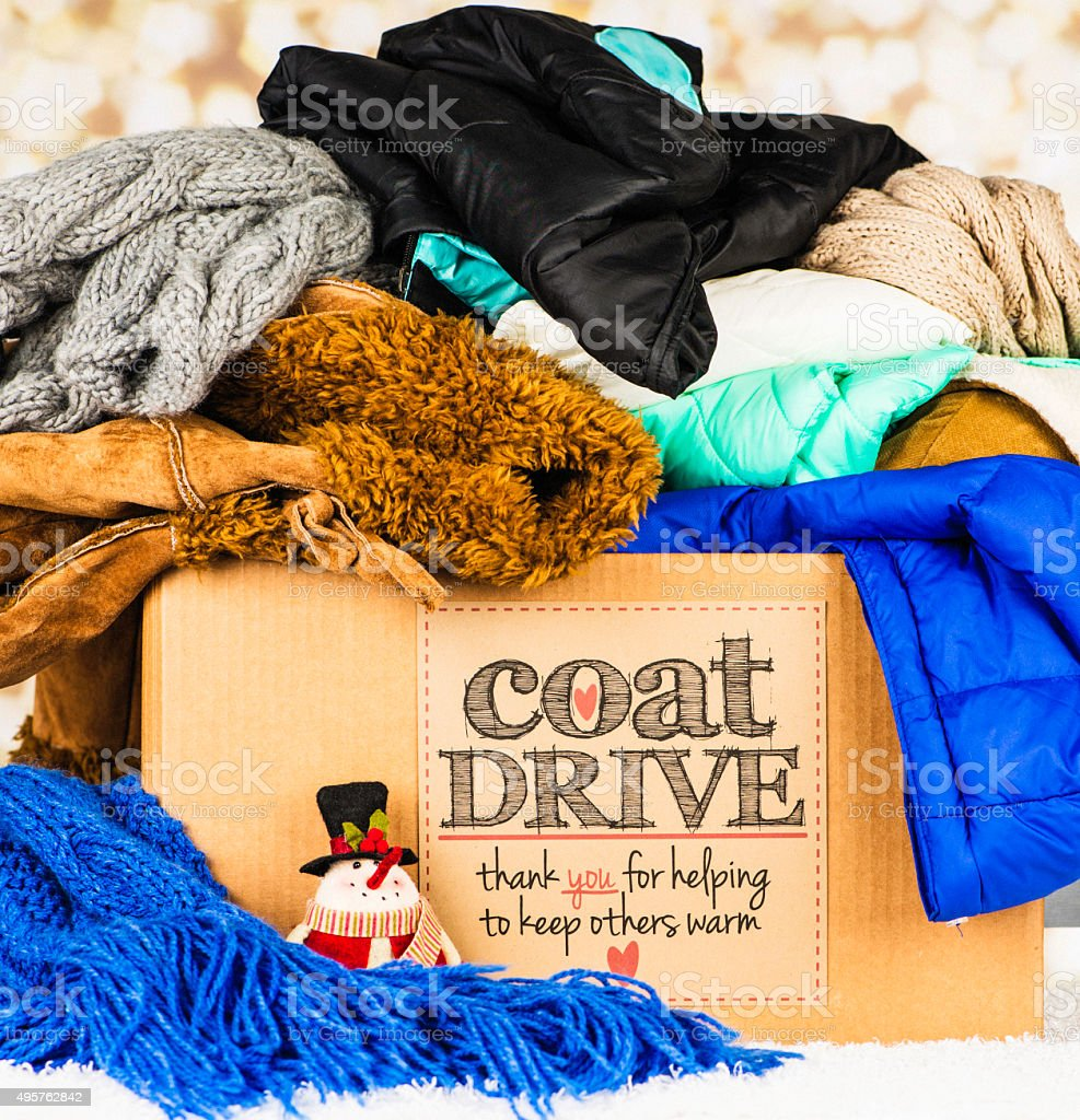 Coat Drive Promotion. Collection box filled with coats and scarves stock photo