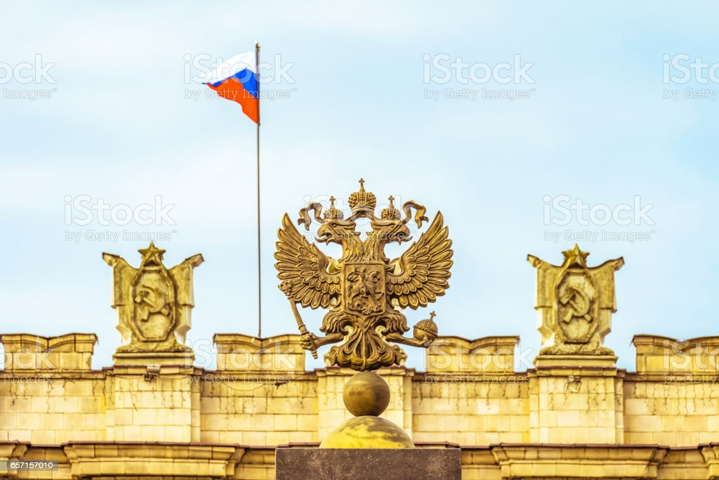 Coat of arms Russian Federation. Coat of arms on background of parapet administrative building government with USSR symbols, Russian flag. Selective focus. stock photo