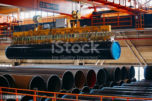 Coated pipe transportation by overhead crane with vacuum handling grippers.