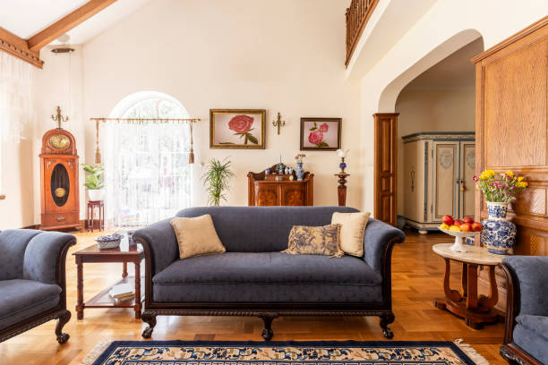 Cobalt blue sofa and other antique furniture on a wooden floor in a spacious living room interior of a classic mansion. Cobalt blue sofa and other antique furniture on a wooden floor in a spacious living room interior of a classic mansion. tradition stock pictures, royalty-free photos & images