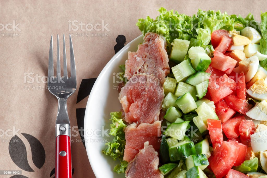 cobb salad - traditional american food,  hearty meal of salmon, eggs, cucumber, avocado and lettuce leaves with mustard dressing, top view stock photo