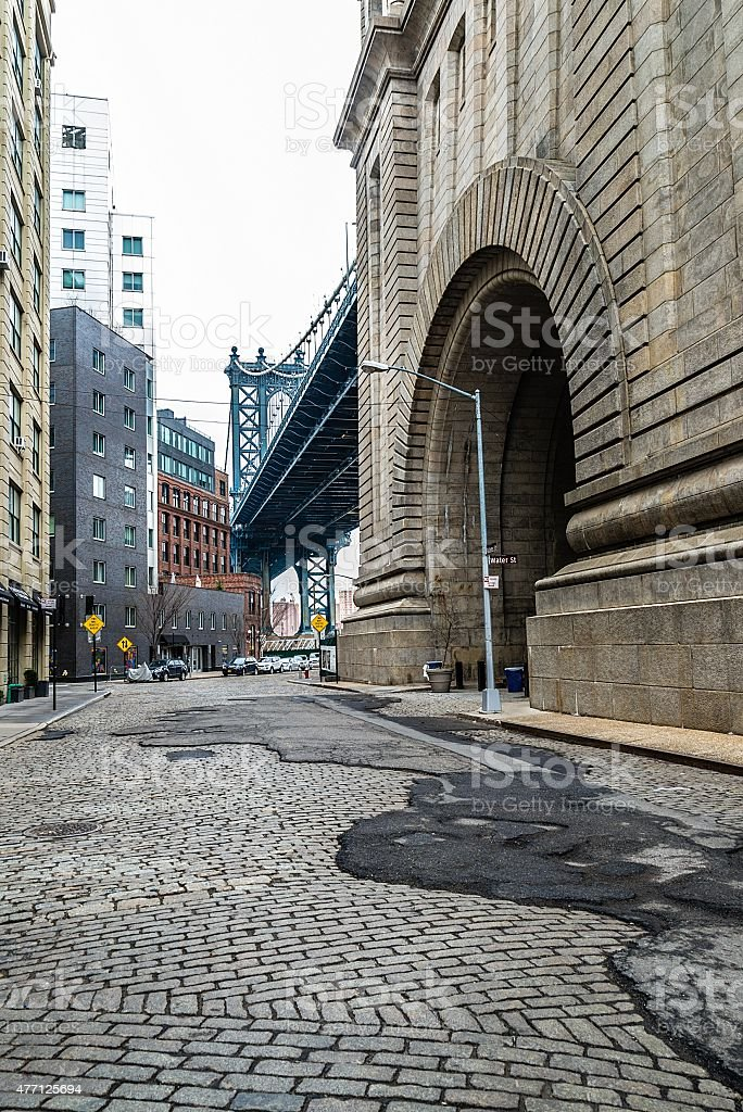 Cobble stone street in Brooklyn under Manhattan Bridge stock photo