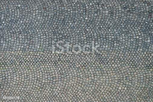 An overhead view of patterned stone cobbles, making up the surface of an old fashioned Paris street.