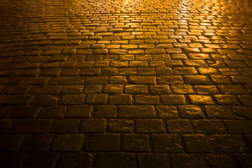 close-up of a cobbled road in the city light, at night