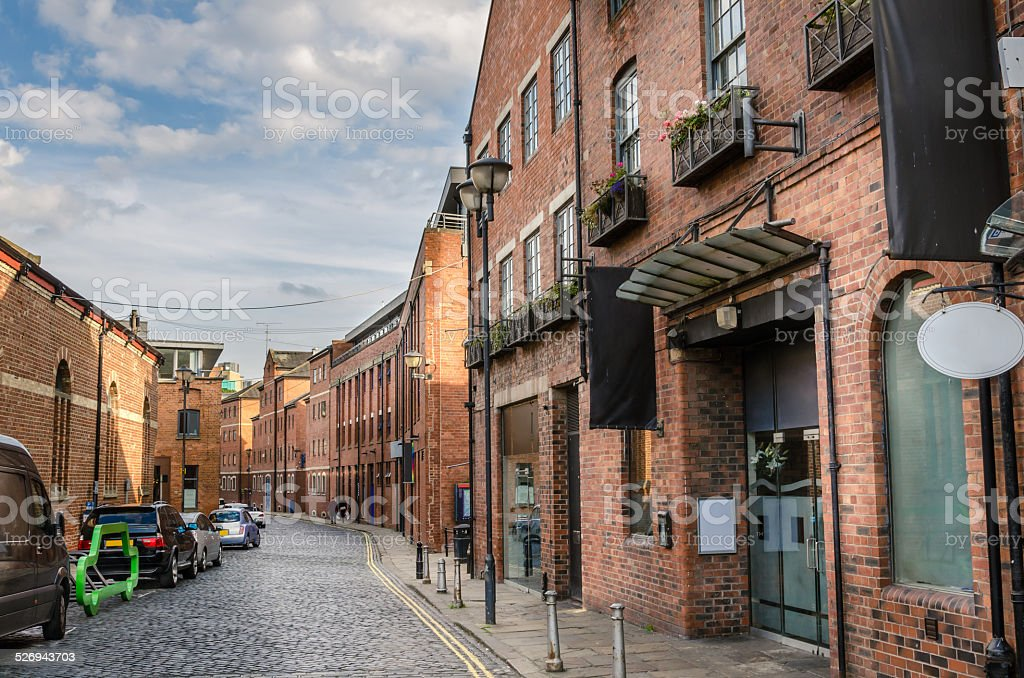 Cobbled Street Lined with Renovated Brick Buildings stock photo