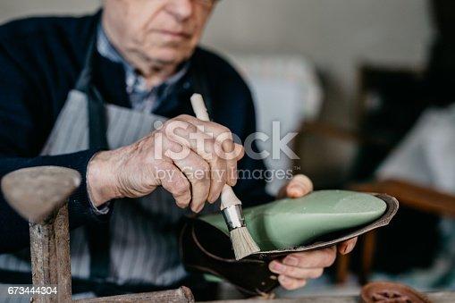 Cobbler holding a brush in hand