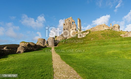 istock Cobblestone path leading up to Corfe Castle ruins on a bright sunny day with bright green grass and no people. 1291937007