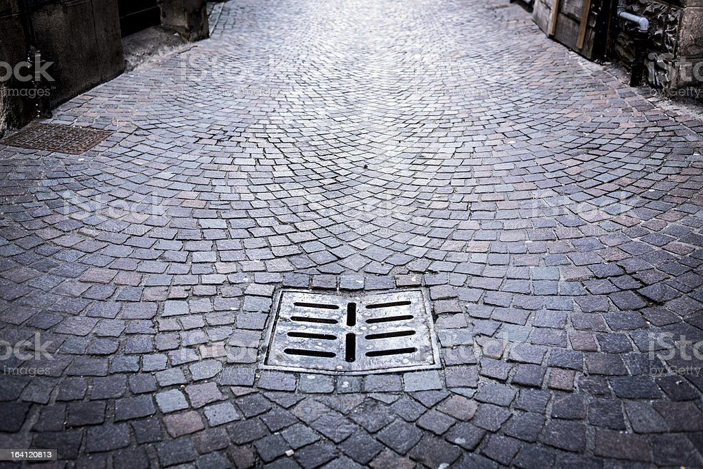 Cobblestone perspective with drain royalty-free stock photo