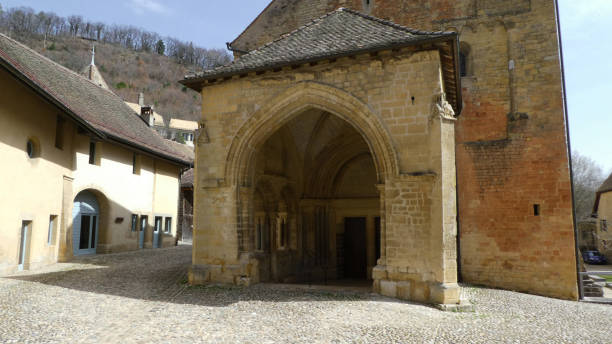 Cobble-stone street and entrance to Romanesque church in Romainmôtier-Envy in the Jura-Nord region of Switzerland stock photo
