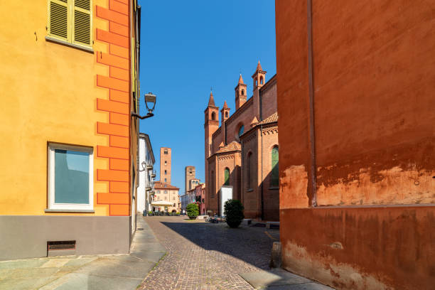 Cobblestone street and medieval towers on background in old historic center of Alba, Italy. stock photo
