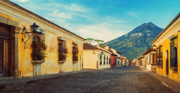 Cobblestone street in Antigua, Guatemala - Acatenango volcano in the back