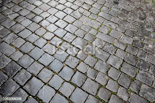 View of feet walking on a cobblestone street in Rome.