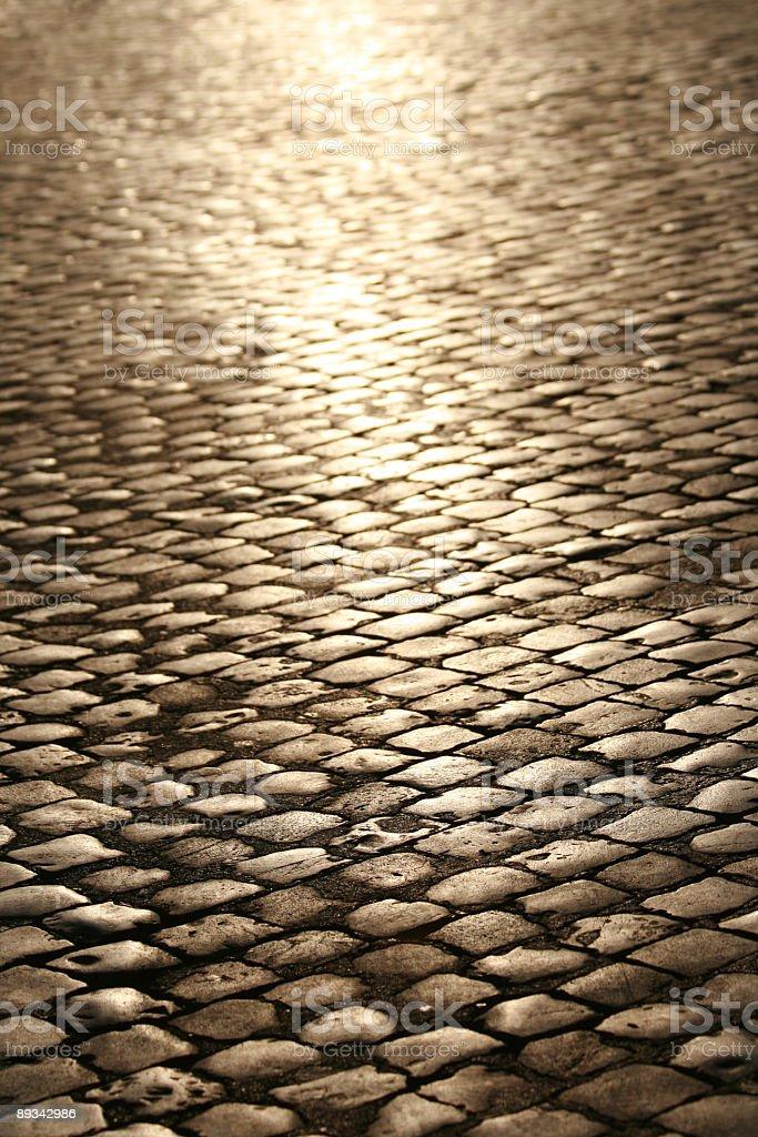 A cobblestone street with a light shining stock photo