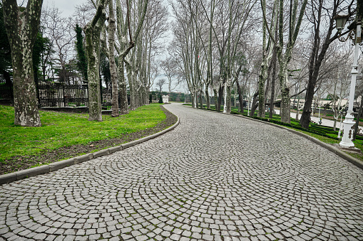 Cobblestone way and path in Gulhane public park with white street lamps and withered and dried trees and green grass during overcast sky and rain and bosporus background.