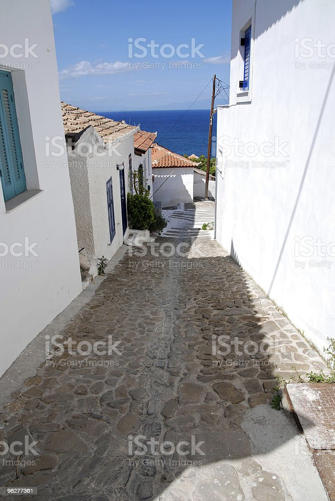 cobblestone way down to the sea in a greek village royalty-free stock photo