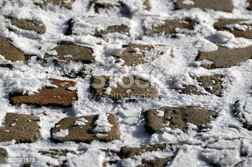 Old Cobblestones covered with snow close up.