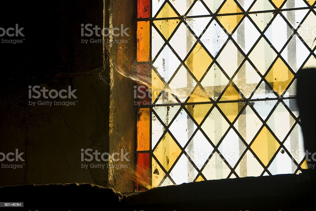 Cobwebs on a stained glass church window. royalty-free stock photo