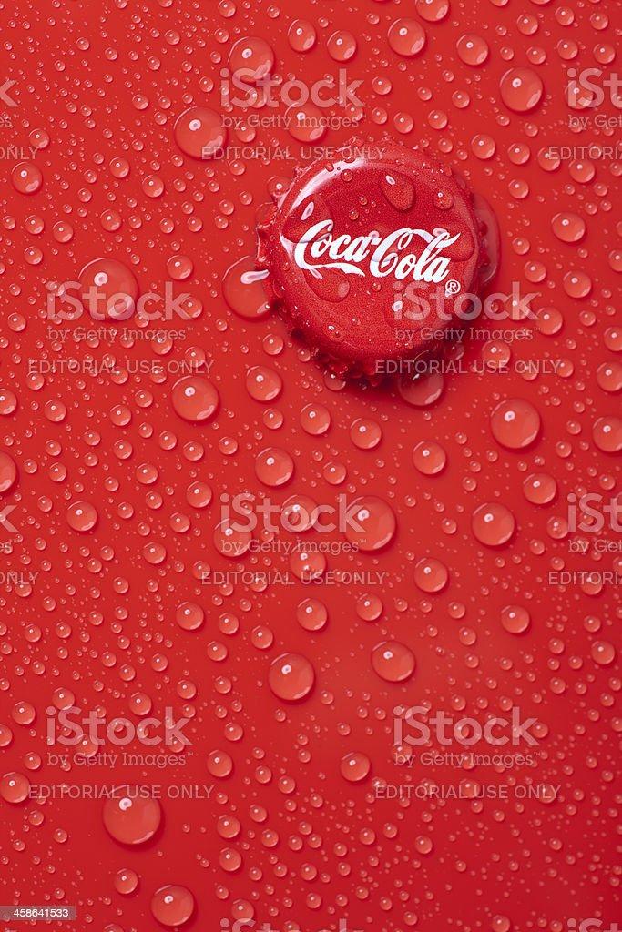 Tapón de botella de Coca Cola sobre superficie roja, húmeda - foto de stock