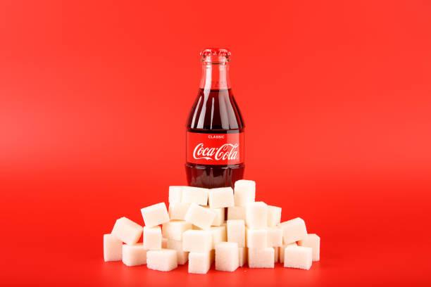 Coca Cola-Flasche mit Stapel der Würfelzucker – Foto