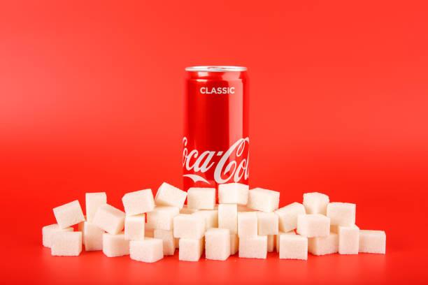 Coca Cola können mit Stapel der Würfelzucker – Foto