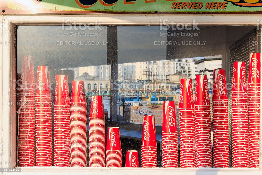 Coca Cola Paper Cups on Display Window Brighton, UK - September 13, 2016 - Coca Cola paper cups on display window of a kiosk on the Brighton Pier Assistance Stock Photo