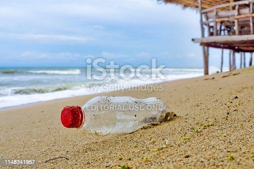 Ko Lanta, Thailand - May 8 2019: One Single use Coca Cola Plastic bottle lies washed up on the beach.  Seemingly harmless, it represents the massive environmental of Global Ocean Pollution.  Plastic in the Ocean is one of the largest threats to our ocean ecosystems.  Up to 12 million tonnes is dumped in the Ocean every year.  Discarded items become dangerous microplastic.  It is responsible for the deaths of huge amounts of Marine Life every year, through entanglement and consumption.  The location here is Ko Lanta, Krabi, Thailand.  I removed the plastic after taking the image.