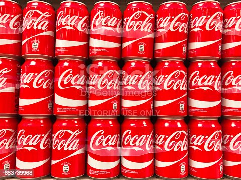 A large group of Coca-Cola red cans stacked in a supermarket in Spain.
