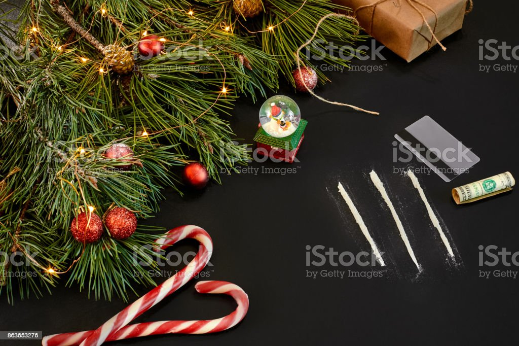 Cocaine divided into paths with Xmas toys and spruce branch on black background top view stock photo