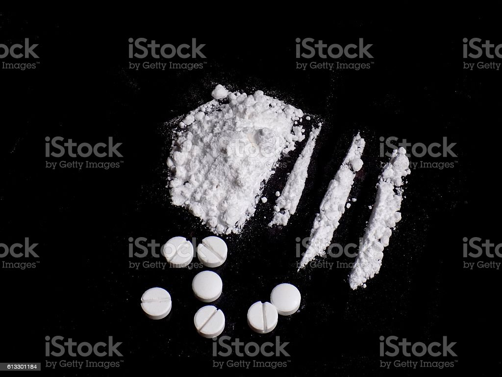 Cocaine drug powder pile and lines, pills on black background stock photo