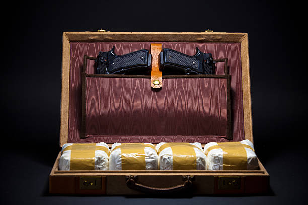 Cocaine Smuggling Still-life shot of a briefcase with kilos of cocaine and two handguns.  Focus on guns. drug cartel stock pictures, royalty-free photos & images