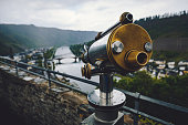 Retro style old and metal tourist coin operated sightseeing telescope looking out over a panoramic city view of historic old town Cochem and Moselle river  in rainy spring time Rheinland-Pfalz Deutschland, Europe