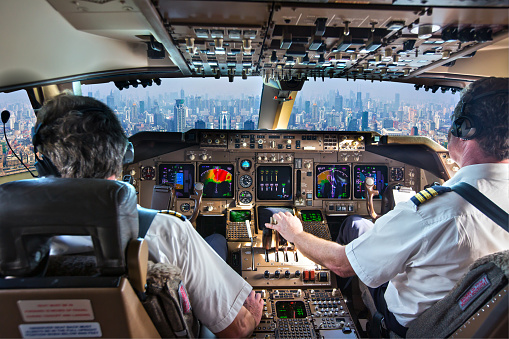 The cockpit of a modern passenger aircraft in flight. A view from the cockpit to the skyscrapers of the business center of a huge city.