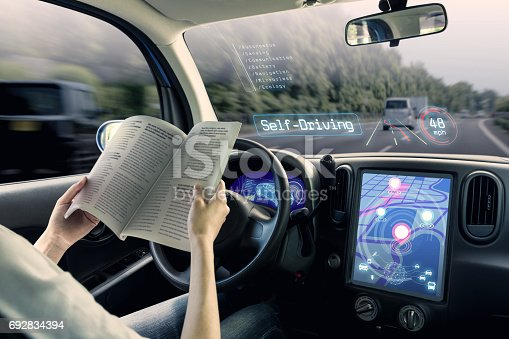 istock cockpit of autonomous car. a vehicle running self driving mode and a woman driver reading book. 692834394