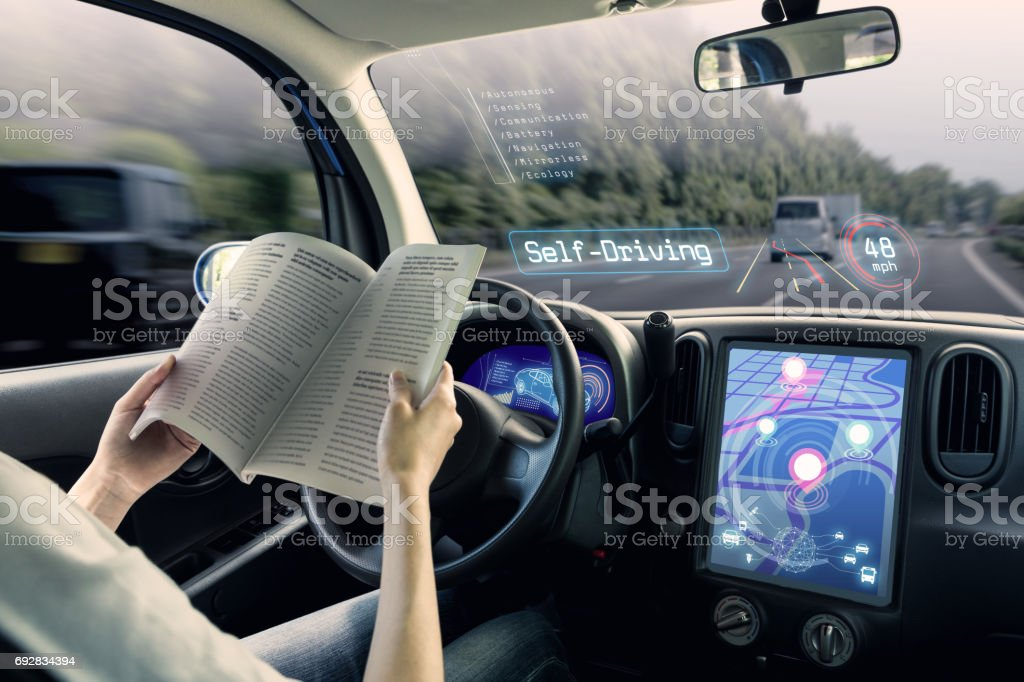 cockpit of autonomous car. a vehicle running self driving mode and a woman driver reading book. stock photo