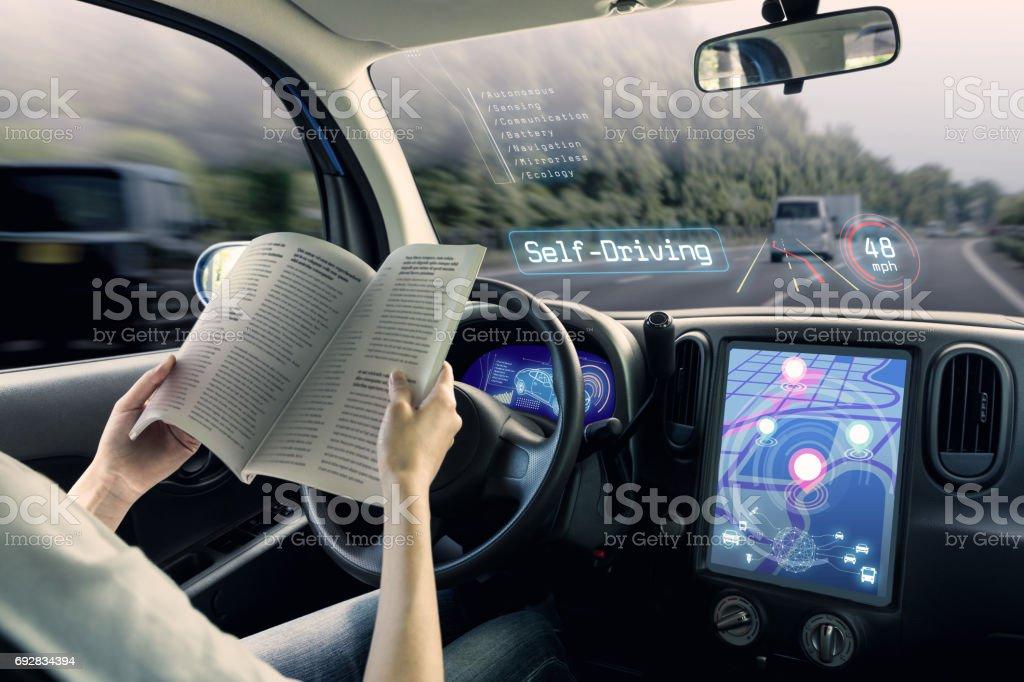 自主車的駕駛艙。一輛行駛自我駕駛模式和一女司機閱讀本書。圖像檔