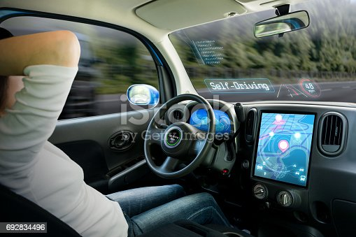 istock cockpit of autonomous car. a vehicle running self driving mode and a woman driver being relaxed. 692834496
