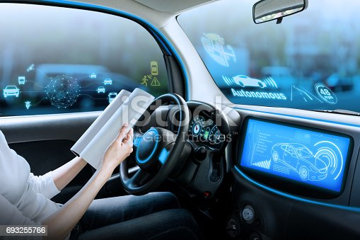 istock cockpit of autonomous car. a vehicle running self driving mode and a woman driver reading book. 693255766