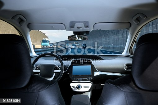 istock Cockpit of driverless car driving on highway viewed from rear seat. 913581054
