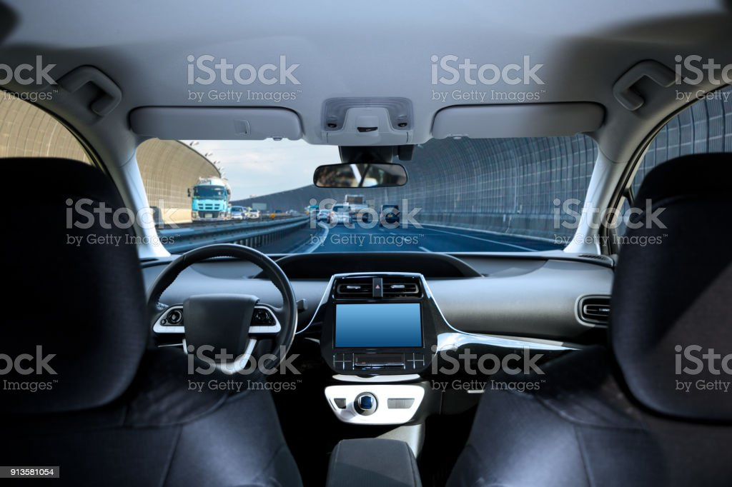 Cockpit of driverless car driving on highway viewed from rear seat. stock photo