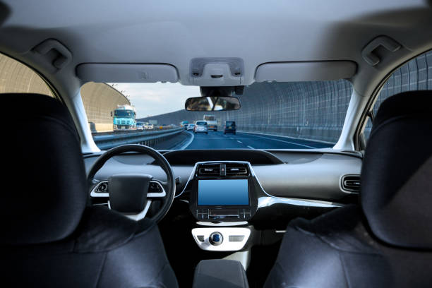 cockpit of driverless car driving on highway viewed from rear seat. - self driving car stock photos and pictures