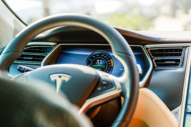 Cockpit of Tesla Model S car Los Angeles, United States - May 17, 2013: A cockpit with LCD digital speedometer and steering wheel of electric car Tesla Model S during drive. Tesla electric cars are produced by Tesla Motors, Inc. in California, USA. tesla motors stock pictures, royalty-free photos & images