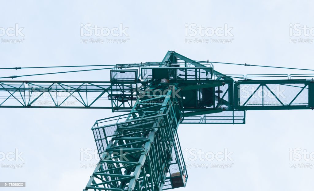 Cockpit photographed from the ground of a green crane in a construction site stock photo